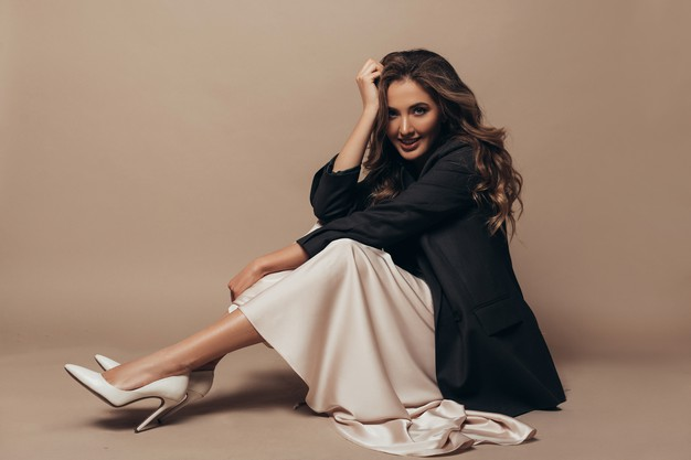 cheerful-model-sitting-floor-wearing-modern-oversize-black-jacket-creamy-long-dress-high-heel-shoes-her-feet-curly-hairstyle-makeup_343629-61
