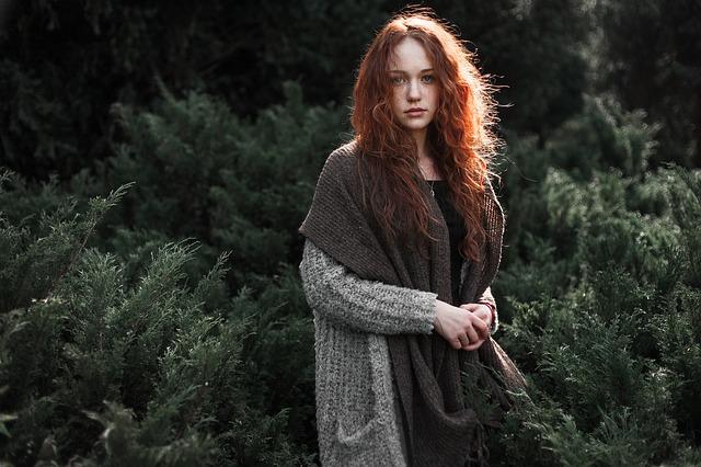 Dievča s dlhými ryšavými vlasmi, v sivom svetri, so šálom stojí pred lesom