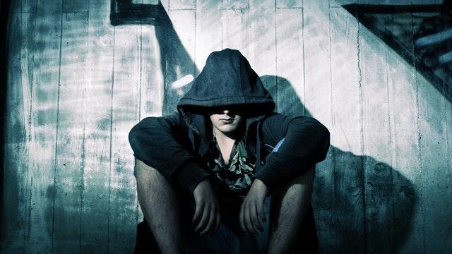 Smutný muž sedí pred stodolou s kapucňou na hlave.jpg
