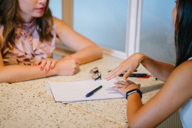 Dve ženy sedia pri stole oproti sebe a rozprávajú sa