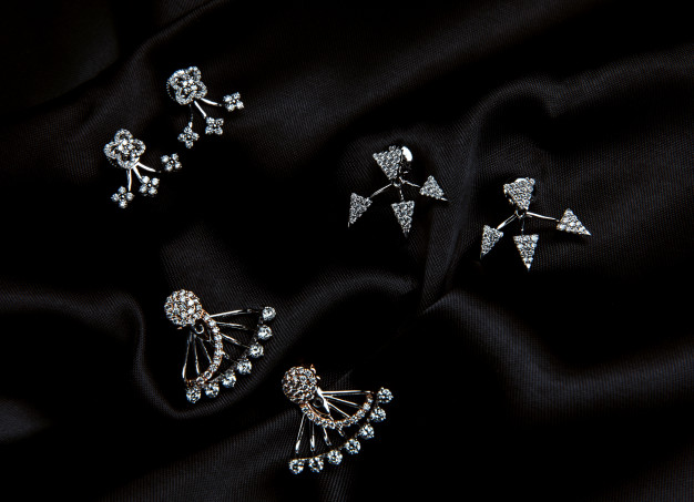 top-view-sterling-silver-earrings-with-swarovski-crystal-with-studs-black-wall_140725-12952